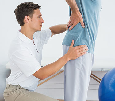 Side view of a male therapist massaging mans lower back in the gym at hospital